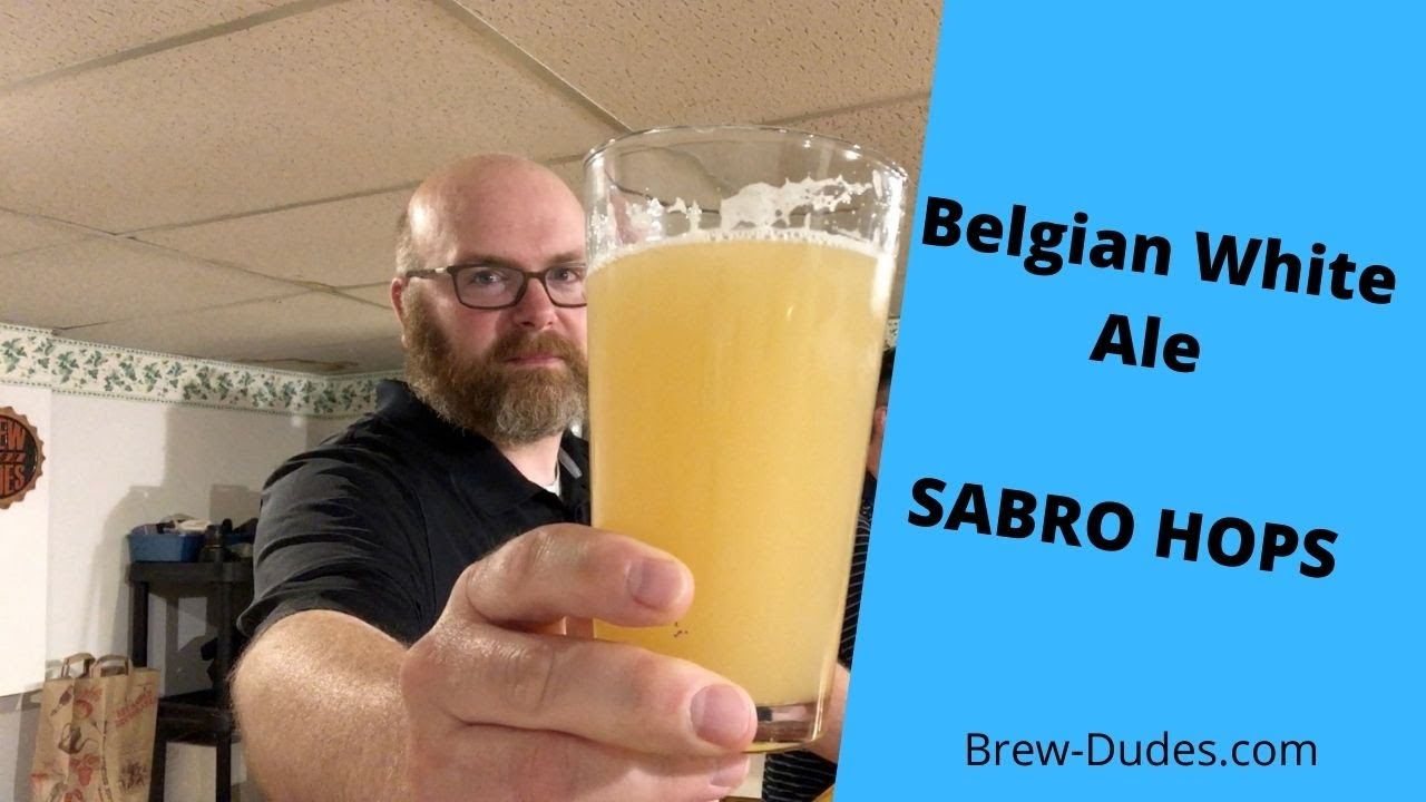 Mike holding up a glass of Sabro Hops White Ale Fermented With Hoegaarden Yeast